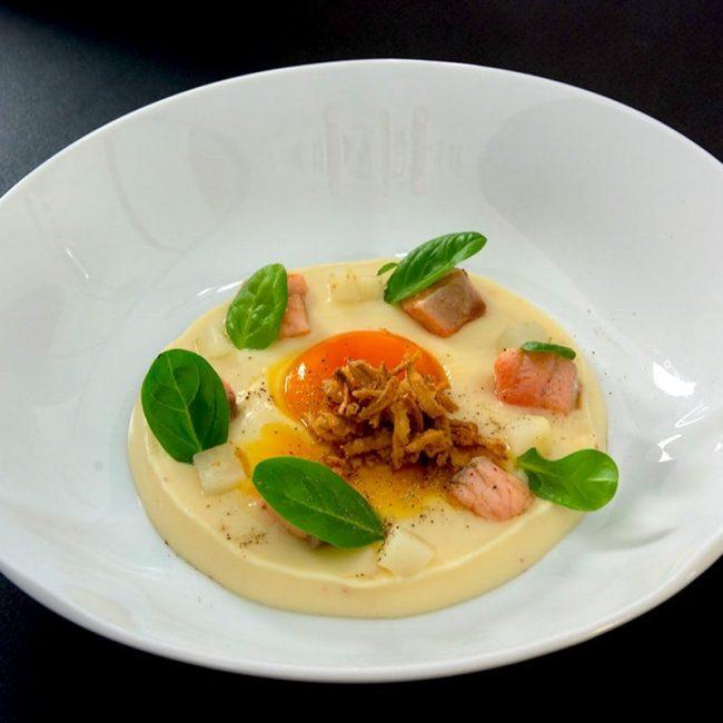 Velours de carottes blanches, jaune d'œuf confit, oignon frit, lardons de saumon frais, brunoise de radis blanc